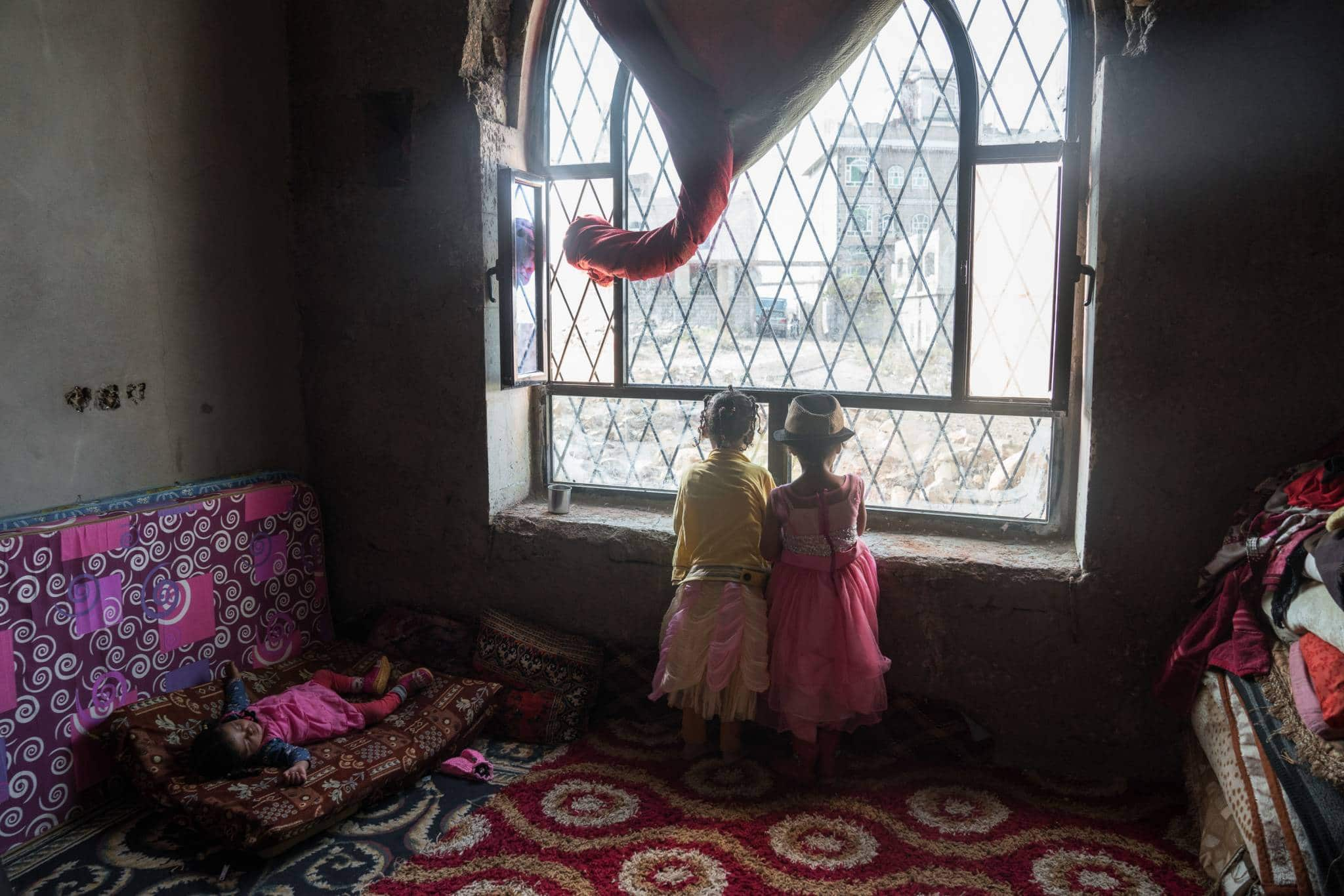 AL ABTHI BUILDING, IBB CITY, YEMEN - 21 APRIL 2017.   Children peer out of a window in a former government building in the suburbs of Ibb. The building was provided by local authorities to house 53 displaced families who fled here from Taizz after heavy fighting flared up in the summer of 2015.   The building has no electricity or running water. The displaced families installed solar panels on the roof of the building to provide power for rudimentary lighting at night. Many of the children help their parents by collecting water and tending to the younger children in the building.