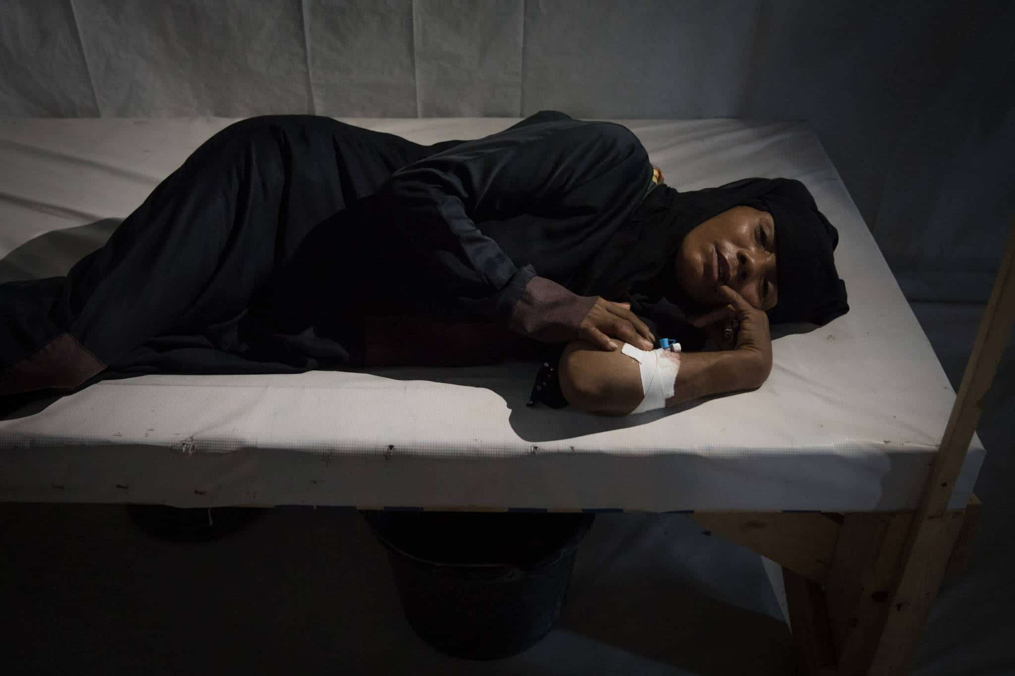 AL THAWRA HOSPITAL, AL HUDAYDAH, YEMEN - 15 APRIL 2017. A suspected cholera patient lies on a wooden bed in a hospital in Al Hudaydah. According to UNICEF figures, as of June 5th 2017, some 70,000 suspected cases of cholera had been reported in the past month alone. That number could quadruple to 300,000 cases by the start of July according to a recent statement by the regional director of UNICEF, Geert Cappelaere. The war is severely hampering access for critical medical supplies.