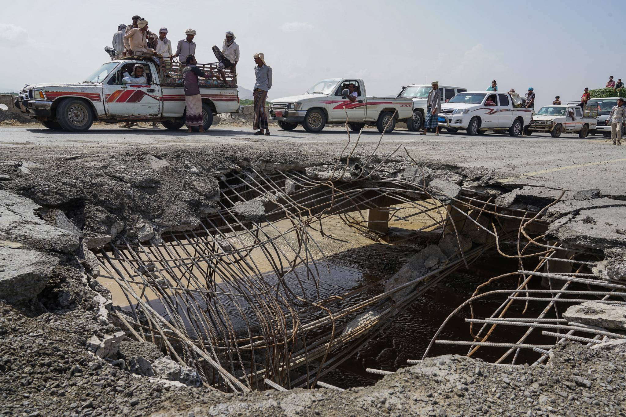 AL HUYDAYDAH TO ABS ROAD, YEMEN -  6 MAY 2017.  Cars and trucks wait in line to pass over a bridge that was hit by an airstrike in 2016.  This road is one of four roads linking Al Hudaydah with the rest of the country.