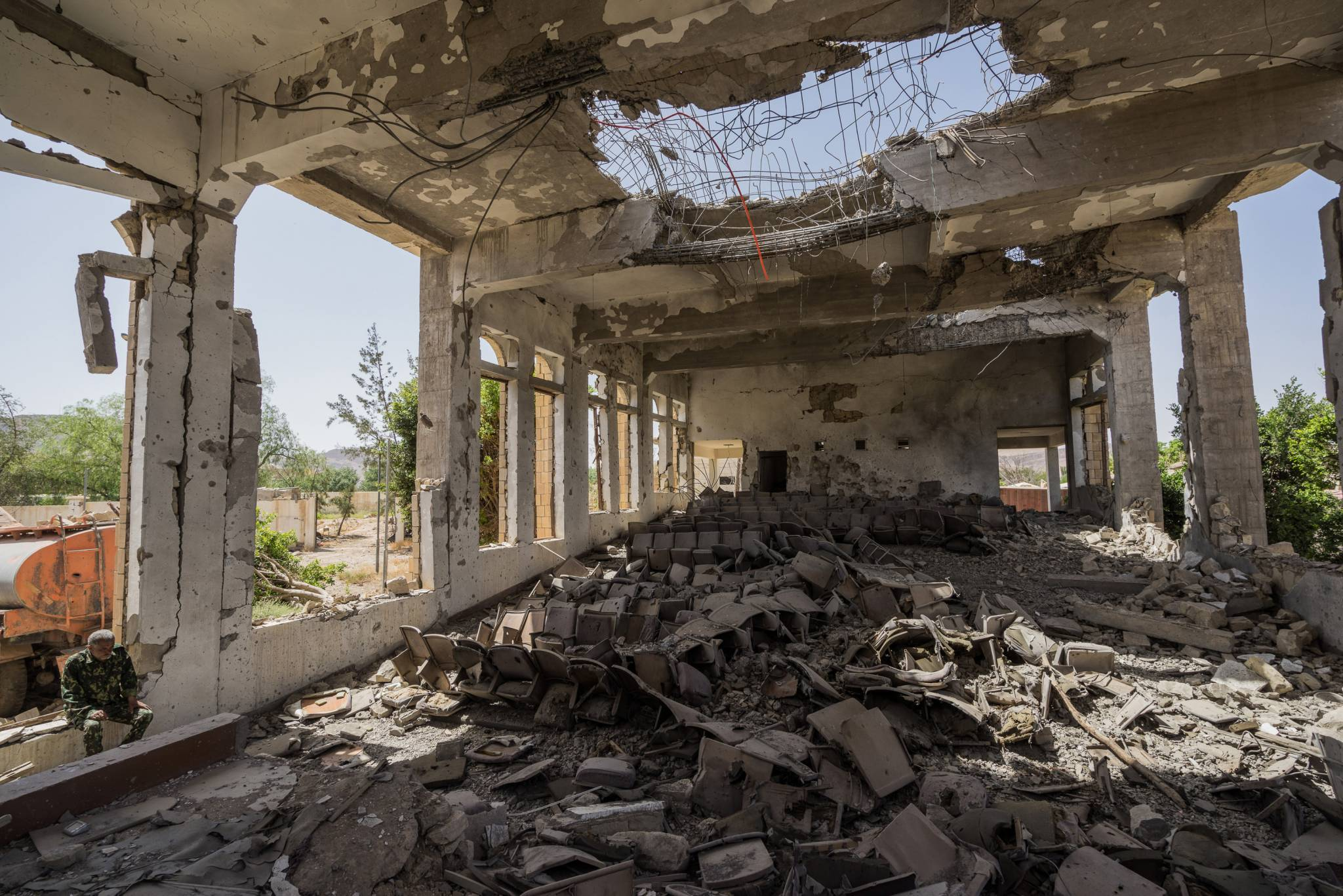 SAADA CITY, SAADA GOVERNORATE, YEMEN. 24 APRIL 2017.   A military guard sits in the former Assembly Hall of the Governor of Saada that now lies in ruins following multiple airstrikes in April 2015.