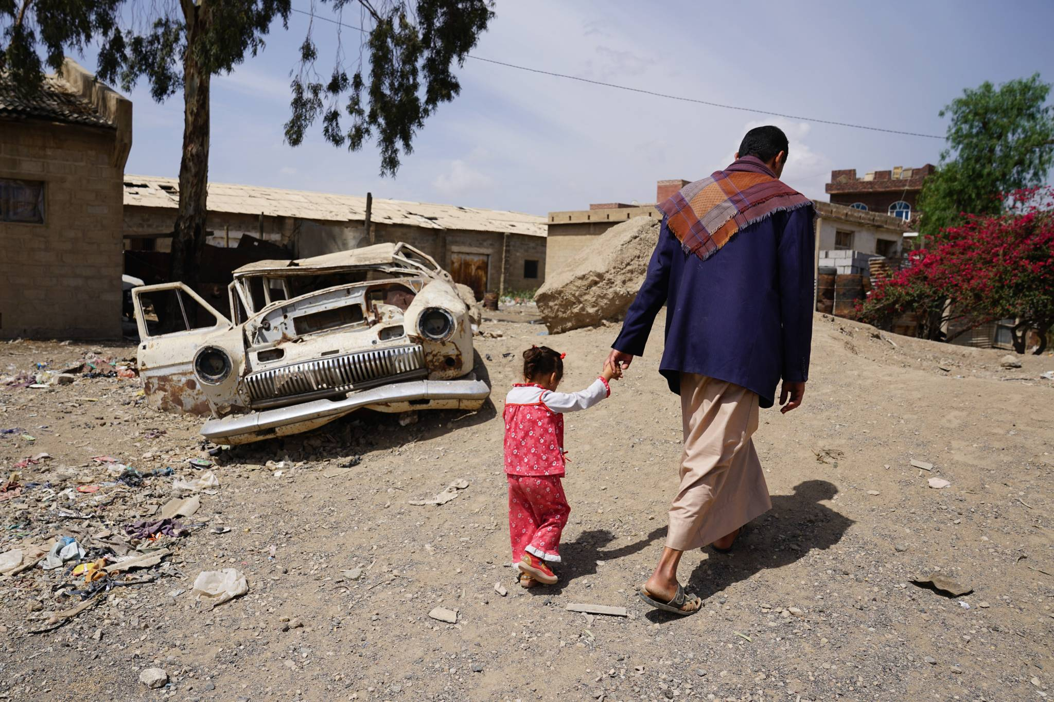 HARAT AL- MASNA'A, YEMEN - 28 APRIL 2017.   Abdellatif Allami walks with his 3-year-old daughter Sara in the Harat Al-Masna'a slum in Sana'a. The slum sits next to a former textile factory and hosts 231 families of former factory workers. The factory, which employed up to 1,600 workers, has been closed since 2005. The former workers used to receive a basic pension of around 30,000 Yemeni rials ($120) per month, but payments stopped seven months ago. Families now rely on donations to survive.